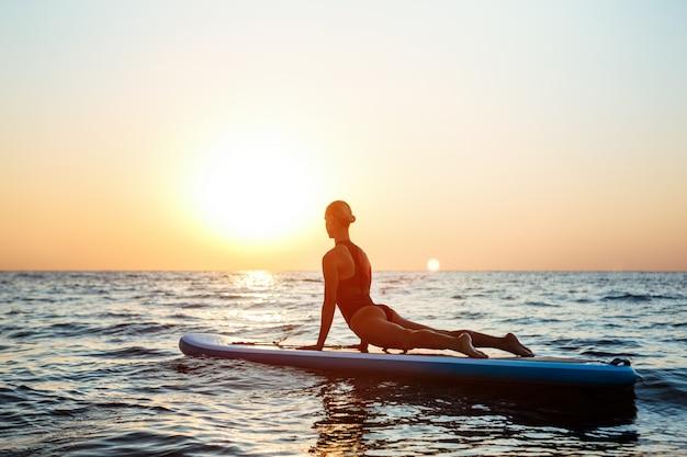 日の出サーフボードでヨガの練習の美しい女性のシルエット。