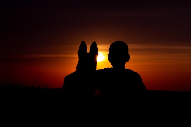日没時に抱き締める少年と犬のシルエット