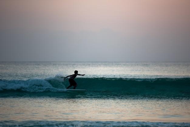 일몰시 바다 해안에서 보드에 서핑하는 소년의 실루엣