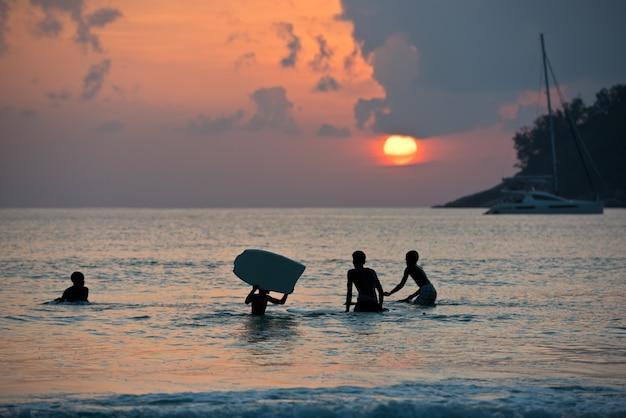 日没時に海岸のボードでサーフィンする男の子のシルエット