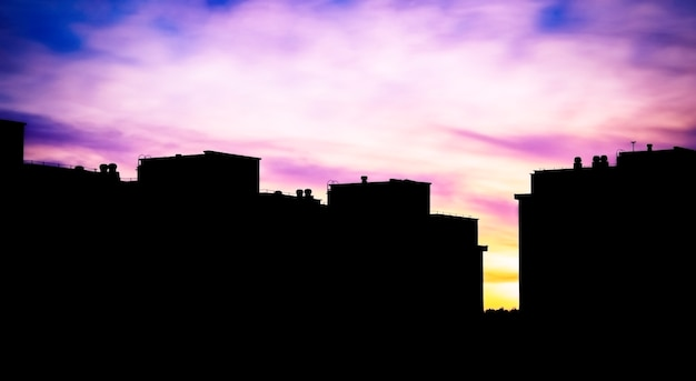 美しい色の明るい空と日没時の建物のシルエット