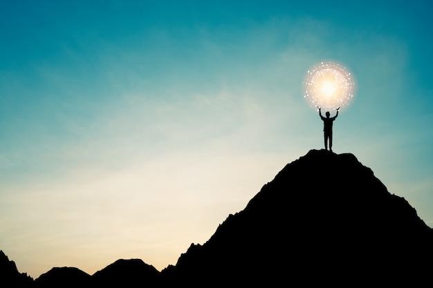 푸른 하늘과 햇빛을 통해 산 위에 세계와 연결 라인을 잡고 사업가의 실루엣.