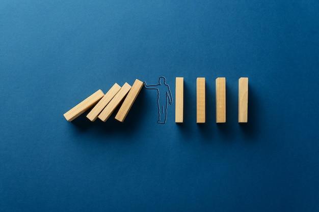 Силуэт бизнесмена на темно-синем фоне останавливает падение домино в концептуальном изображении