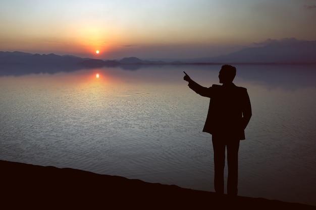 일몰 하늘 배경으로 호수에 뭔가 가리키는 사업가의 실루엣
