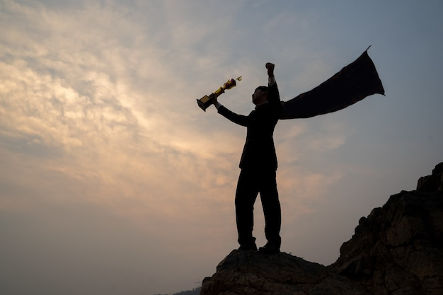 트로피 컵, 성공 및 리더십 개념을 들고 산에 서 있는 사업가의 실루엣.