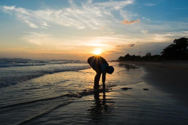 해변에서 아래로 구부리는 아이의 실루엣