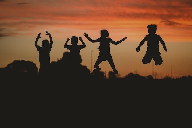 Силуэт детей, позирующих на холме в окружении зелени во время золотого заката