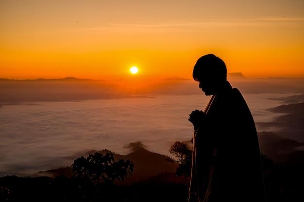日没で祈るキリスト教の男のシルエット