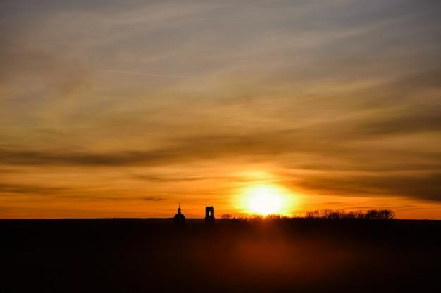 日没の背景に教会のシルエット日没時にフィールドに放棄された教会