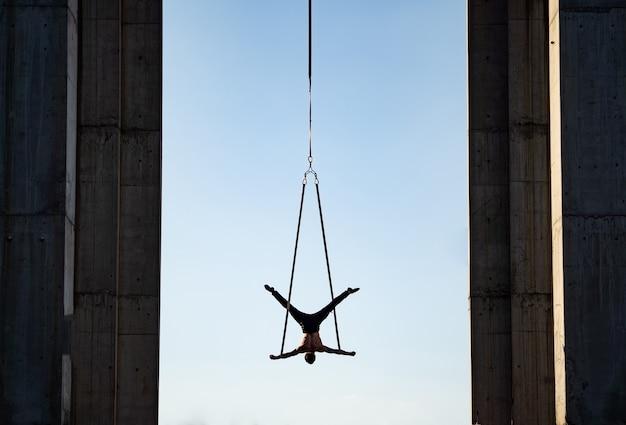 Силуэт артиста цирка на воздушных ремнях на фоне голубого неба и столбцах концепции искусства и перформанса Premium Фотографии