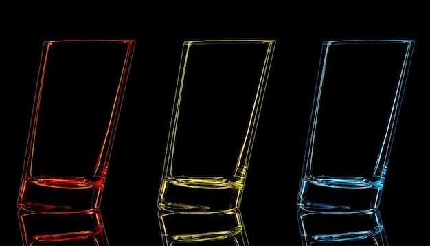 黒の背景で撮影するためのカラーガラスのシルエット。