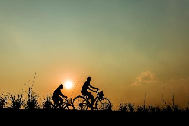 Силуэт пара вождения велосипед счастливое время закат