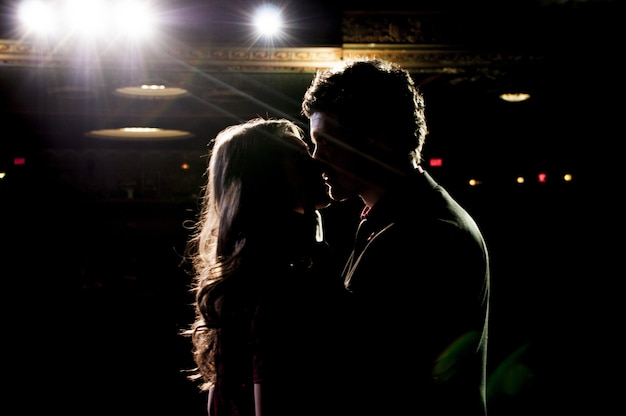 Силуэт пары, целующейся, стоя на сцене в театре