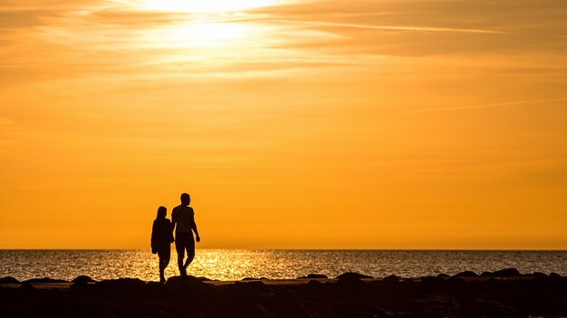 Силуэт пара прогулки на пирсе во время золотого часа заката