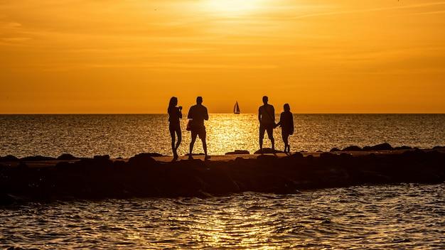 Силуэт пар, идущих на пирсе во время золотого часа заката