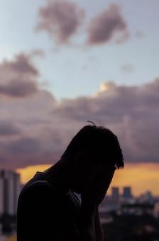 雲の空と街の背景と泣いている落ち込んでいる男のシルエット