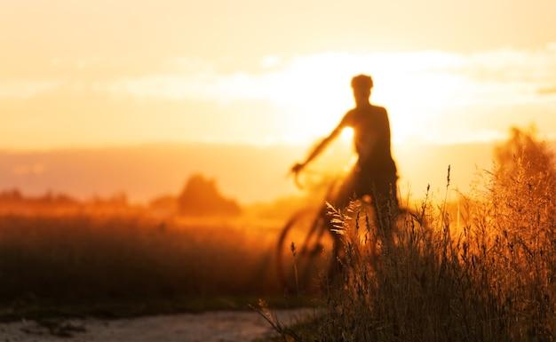 砂利自転車のサイクリストのシルエットは、美しい夕日のフィールドに立っています
