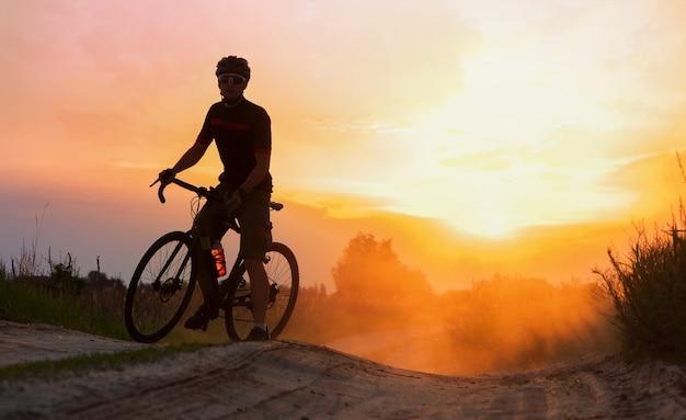 Силуэт велосипедиста, едущего по следу пыли на фоне заката.
