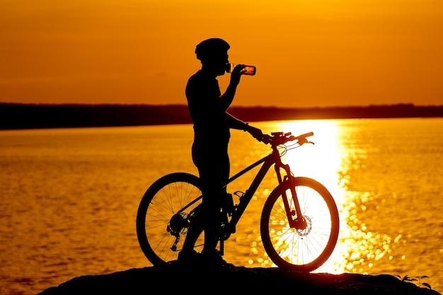 일몰 자전거의 실루엣입니다. 남자는 물을 마시고 있습니다. 백그라운드에서 강입니다. 라이프 스타일 개념.