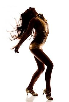 Силуэт танцующей стройной красивой женщины в сексуальном золотом костюме и туфлях на средних каблуках, изолированных на белой стене
