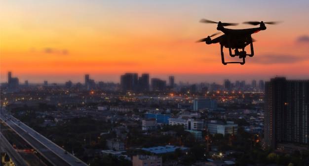 夕暮れ時の街の上を飛んでいる無人機のシルエット