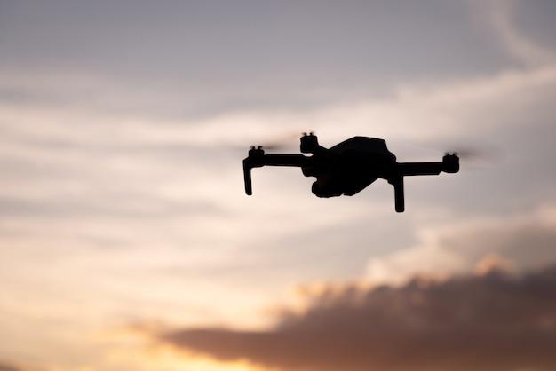 파란색 약간 흐린 하늘에 떠 있는 무인 항공기의 실루엣. 높은 곳에서 동영상과 사진을 만드는 새로운 기술.
