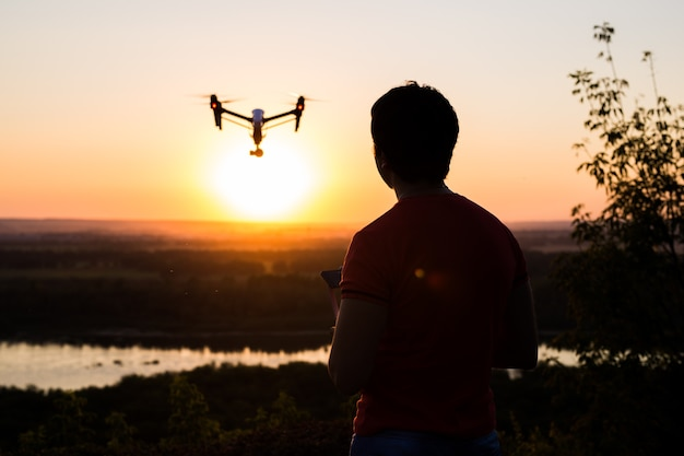 空を飛んでいる写真カメラとドローン、クワッドコプターのシルエット。