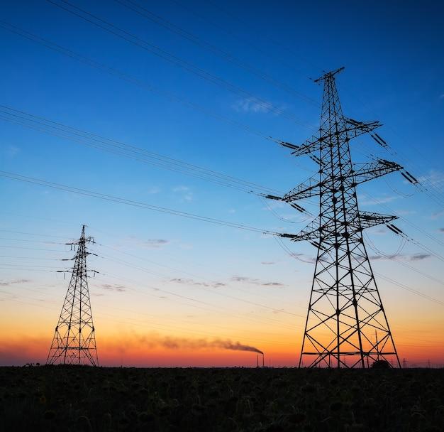 전기 pylons 및 일몰에 분야에 고전압 전력선의 실루엣. 일출에 전기 에너지 배선