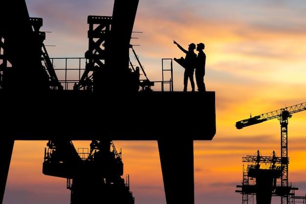 重いインフラストラクチャの建設現場の背景、夕方の日没時の建設現場でのエンジニアと労働者のチェックプロジェクトのシルエット。