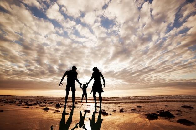Силуэт семьи, играя на пляже
