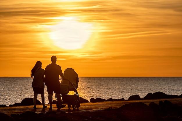 Силуэт семьи, прогулки по пирсу во время золотого часа заката