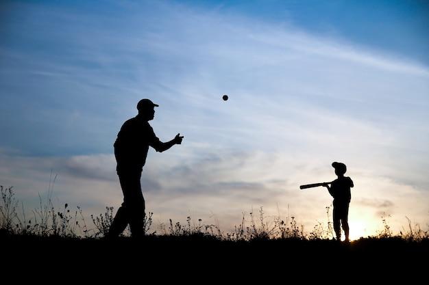 자연 가족 스포츠 개념에 야구를 하는 아버지와 아들의 실루엣
