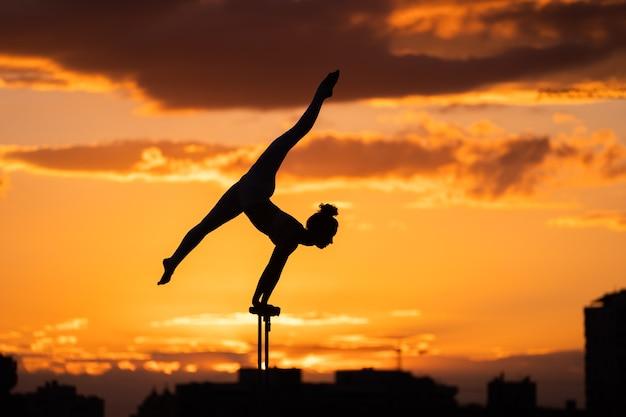 일몰 동안 극적인 하늘 배경에 손으로 하 고 여성 서커스 예술가의 실루엣