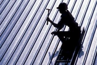 錫屋根を打つ女性建設労働者のシルエット