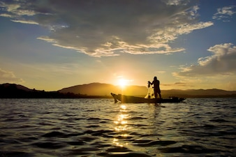 Silhouette of fisherman throwing fishing net in Thailand