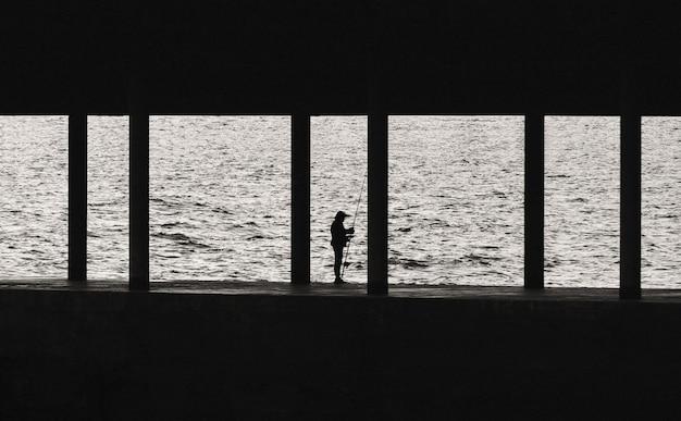 桟橋に釣り竿を持つ漁師のシルエット。海の背景に孤独な古い漁師。黒と白の写真。