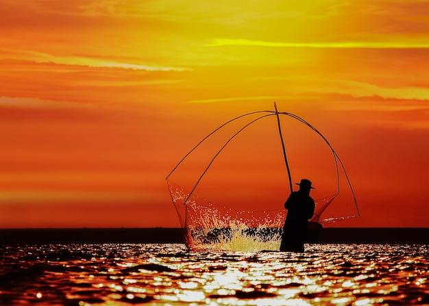 釣り道具を使用して、黄金の太陽が輝いている間の漁師のシルエット