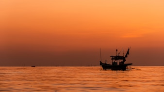Silhouette of Fishing boat with sunset in thailand.