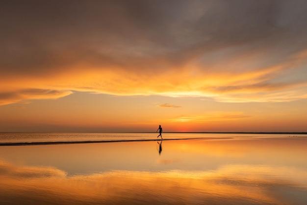 Силуэт женщины фитнеса, бегущей на пляже на закате