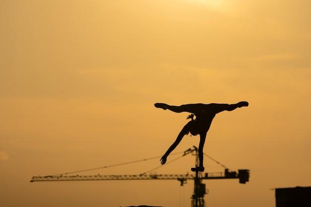 Силуэт гибкого акробата, делающего стойку на руках на фоне драматического заката концепции willpowe ...