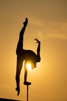 Силуэт гибкого акробата, делающего стойку на руках на фоне драматического заката. понятие силы воли, контроля и мечты.
