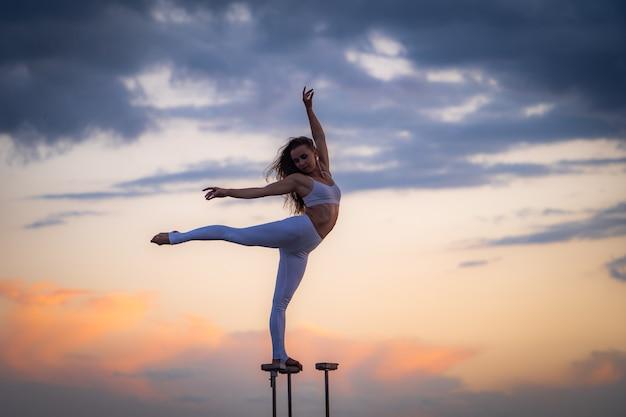 Силуэт гибкой и подтянутой девушки, стоящей на фигуре с расколом и сохраняющей баланс на фоне драматического заката. концепция йоги и здорового образа жизни.