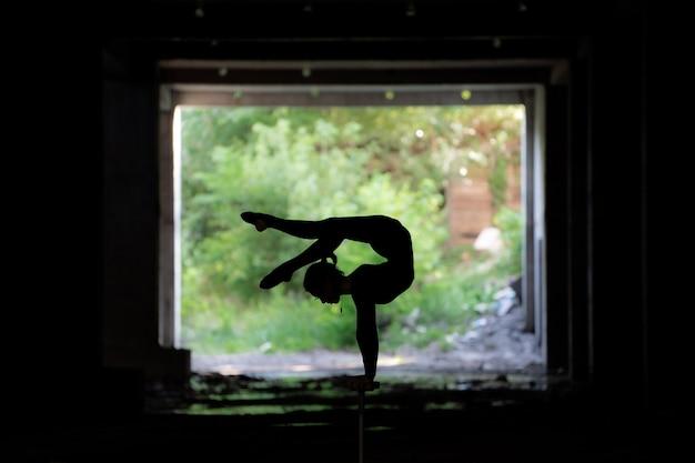 Силуэт гибкого циркового артиста, делающего стойку на руках, концепция индивидуального творчества и выдающегося
