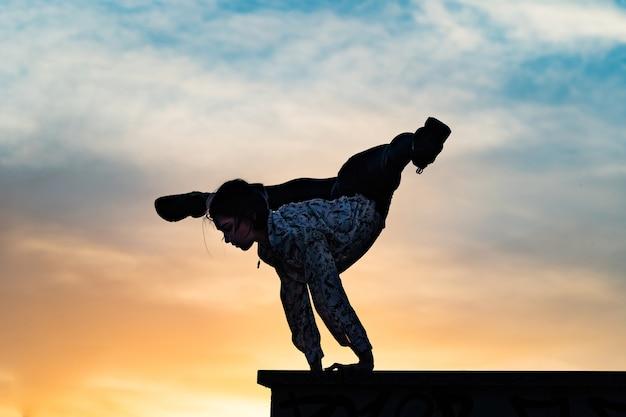 Силуэт гибкой цирковой артистки делает стойку на руках на фоне драматического заката в индивидуальном ...