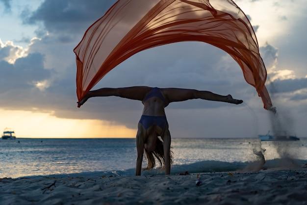행복의 자유와 평온함의 바다 배경 개념에 폭풍우 구름과 함께 극적인 일몰 동안 실크와 물구나무를 하는 유연한 맞는 여성의 실루엣