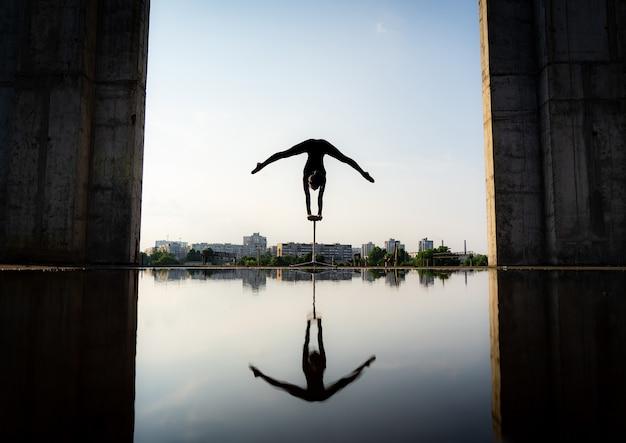 Силуэт гибкой стойки на руках донг девушки в расколе на фоне неба. понятие силы воли, мотивации и страсти.