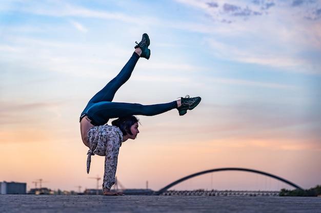 Силуэт гибкой женщины, делающей стойку на руках на драматическом закате и концепции городского пейзажа ...