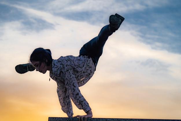의지력 운동의 극적인 일몰 개념에 물구나무서기를 하는 유연한 여성 체조 선수의 실루엣...