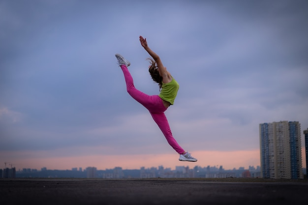 일몰 동안 극적인 클라우드스케이프에서 점프하는 유연한 여성의 실루엣