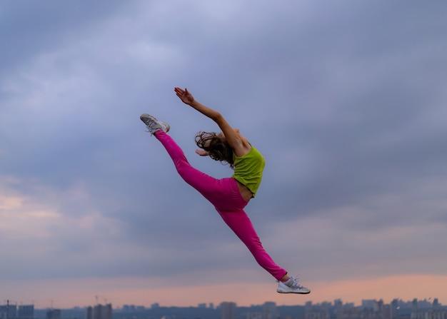극적인 클라우드스케이프에서 점프하는 유연한 여성의 실루엣입니다. 흥분 개념